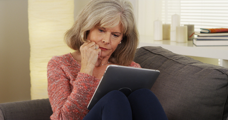 Beautiful mature woman tablet reading