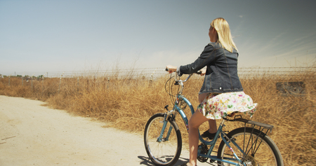 Young blonde caucasian woman riding bicycle in dry environment