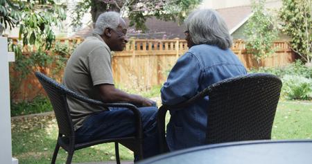 Happy eldery black couple talking in the backyard 免版税图像