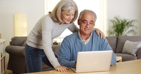 Mature couple using laptop computer together 免版税图像