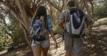 Young backpacker boyfriend and girlfriend hiking through dense forest trail