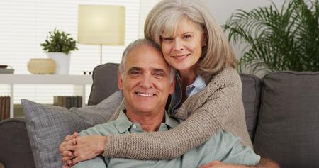 Senior couple hugging and looking at camera