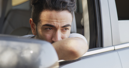 Attractive Mexican man sitting in car looking out 免版税图像