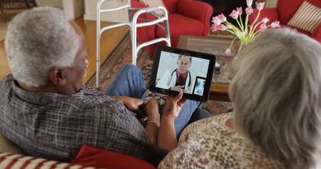 Mature black couple consulting doctor on a tablet 免版税图像