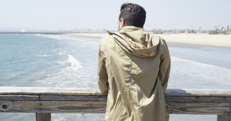 Young Hispanic man staring into horizon from a pier