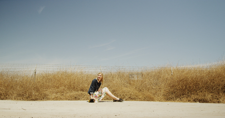 Young blonde hip girl sitting in middle of road 免版税图像