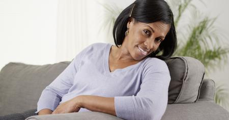 Portrait of comfortable black senior woman sitting on sofa 免版税图像