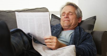 Mature mid-aged man lying on a couch reading the newspaper