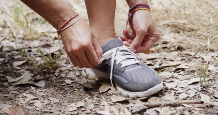 Active fit woman tying shoe in the park