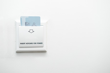 Keycard insert to power switch for control of the electric in the room on white background