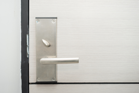 Stainless steel door handle in hotel with electronic card lock on wooden door