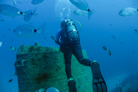Scuba diver near the funnel of a sunken tugboat.