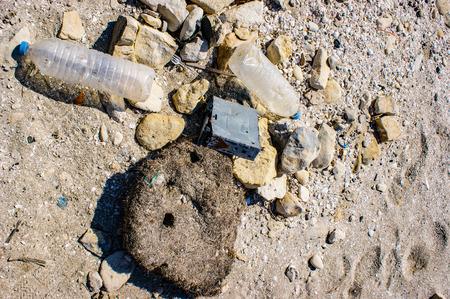 Plastic bottles and a broken car radio litter the beach.