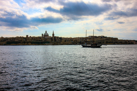 Valletta skyline and boat almost silhouetted against the sky Редакционное