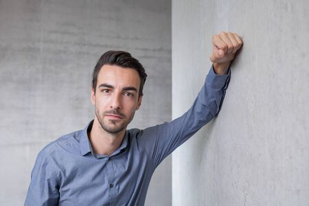 콘크리트 벽에 기울고 젊은 남자 스톡 콘텐츠