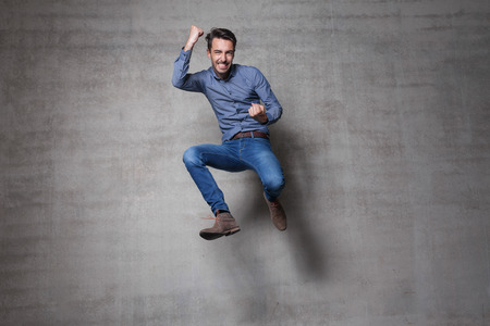 happy people jumping: euphoric business man jump wall