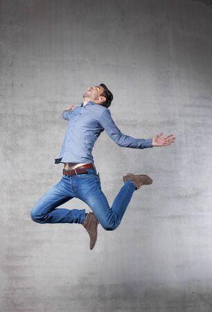벽 앞에 젊은 남자 점프 스톡 콘텐츠