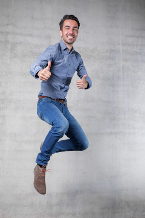 thumps up: thumps up jump of a happy business man Stock Photo