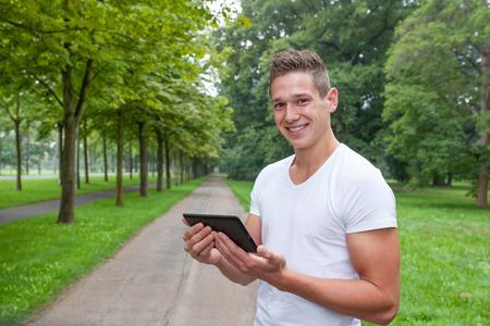 젊은 남자 태블릿 컴퓨터에 애플 리케이션과 그의 훈련을 검사