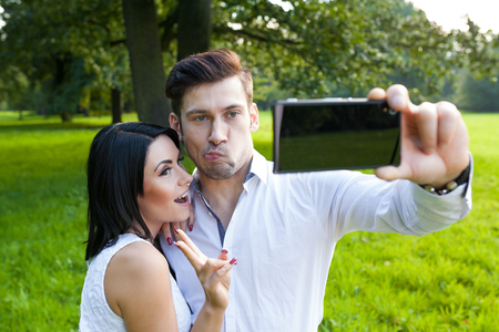 pulling faces: couple in park taking a selfie and pulling faces Stock Photo