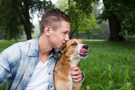 cuddles: young man kissing his dog