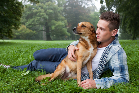 cuddles: young man cuddeling with his dog Stock Photo