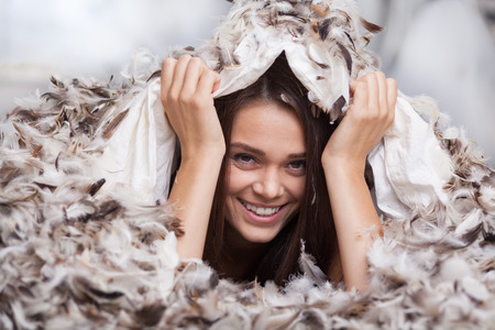 weightless: girl hiding under a duvet with feathers