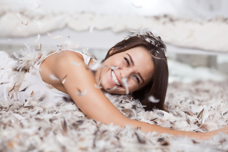 laughing woman having fun with feathers