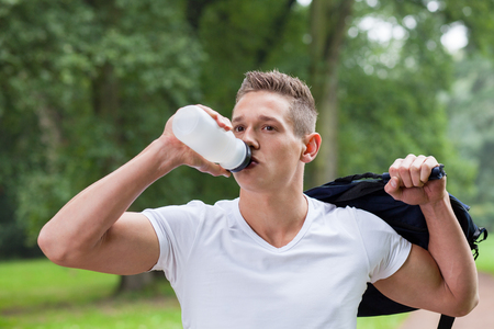 man drinking water: young sporty man drinking water Stock Photo