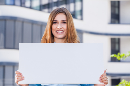 successfull: young business woman holding white sign