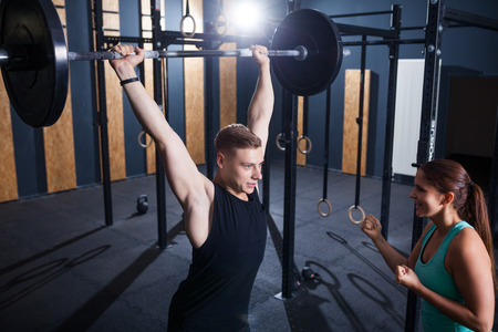 sportwoman: sportwoman cheering for sportsman with barbell at gym Stock Photo