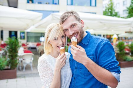 ice cream eating couple with ice cream parlor or Caf� � in city Stock Photo