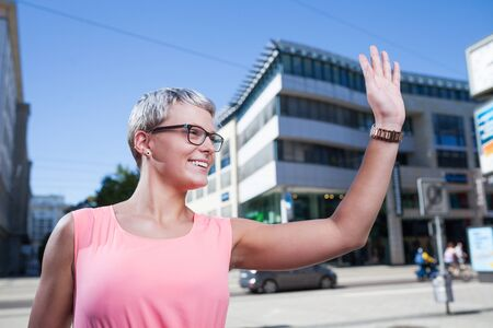 젊은 유행 여자가 택시를 향해 흔들며 스톡 콘텐츠