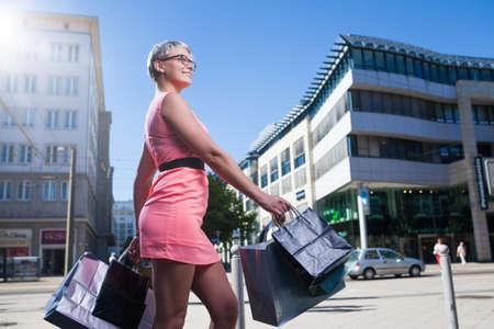 도시에서 treets 산책하는 쇼핑 가방을 가진 소녀