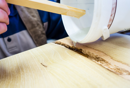 fill fill in: carpenter using clear varnish to fill in holes in wood board