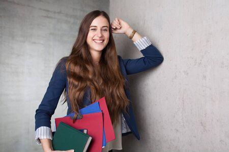 도 서 및 그녀의 팔 아래 폴더를 들고 벽에 기울고 여성 학생 스톡 콘텐츠