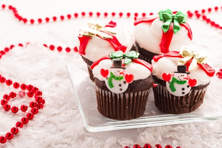 Plate of Chocolate Christmas Cup Cakes with Bows of Red, Gold and Green Stock Photo