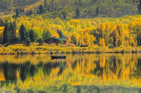 Fishing in a rowboat with brilliant aspen trees behind a lake with reflection