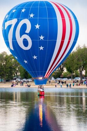 phillip rubino: Decorated hot air balloon skimming over the water