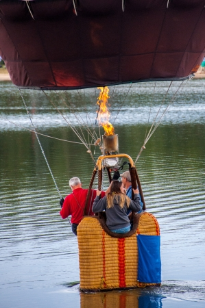 People in a hot air balloon basket skimming over the water Editorial