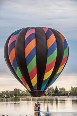 phillip rubino: Striped hot air balloon skimming across a lake