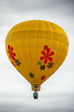 Yellow daisy hot air balloon rising in the sky