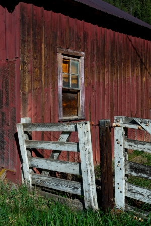 Old red fence and window of a barn photo