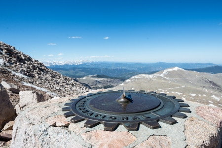Sun dial with Rocky Mountain vista in the background Stock Photo