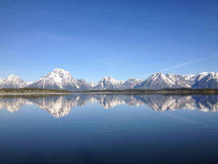Grand Tetons mountain range at sunrise reflecting on the lake.