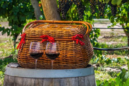 phillip rubino:  picnic basket and 2 glasses of red wine sitting on wine barrel Stock Photo