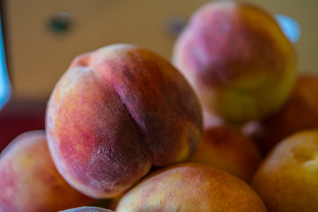 Basket of fresh local grown peaches for sale  in a farmers market