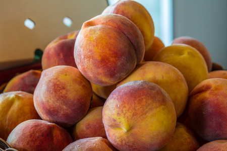 a stack of Ripe local grown peaches ready for farmers market
