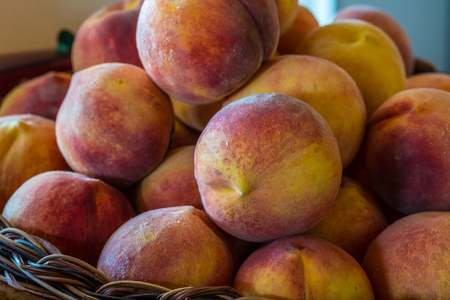 phillip rubino: A basked of Ripe local grown peaches ready for farmers market Stock Photo