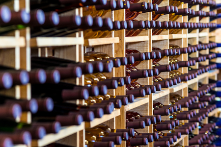 crates of wine bottles stacked against a wall in a row Stock Photo